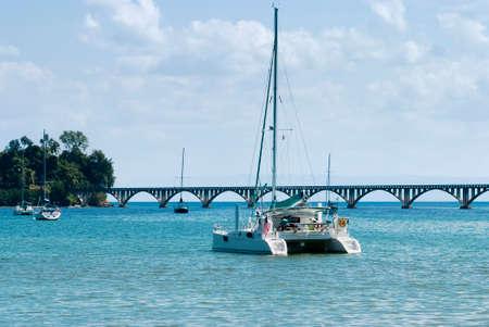 View of a catamaran and sail boats ancored at Samana Bay and  Los Puentes bridge at the background, Samana, Dominican Republic.