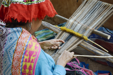 Peruvian woman in traditional clothing weaving cloth on a hand loom in the Andes Mountains, Peru