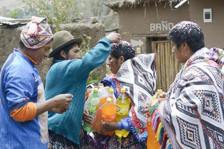 quechua: Traditional Quechua Wedding Ceremony. Indigenous woman putting confetti in the bride`s mother hair. October 22, 2012, Paru Paru, Peru