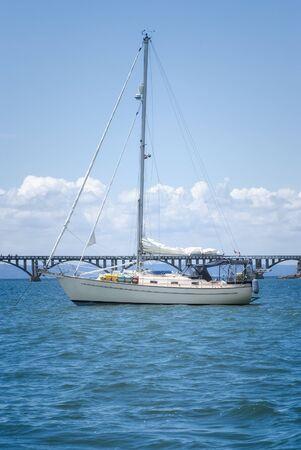 View of a sail boat ancored at Samana Bay and Los Puentes bridge at the background, Samana, Dominican Republic.