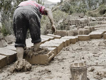 pisaq: Boy making traditional adobe mud bricks in Paru Paru Community Village, Pisaq district, Cusco region. October 22, 2012 - Peru