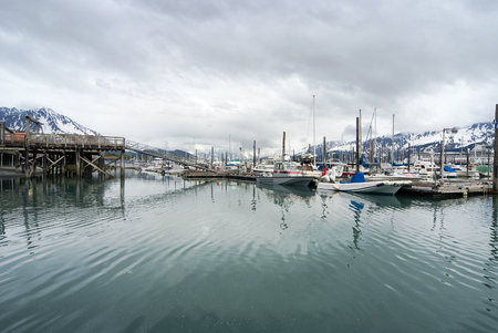 snow covered mountains: View of fishing boats moored at the port of Seward and snow covered mountains behind, Alaska