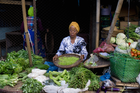 Indonesian woman selling fresh vegetables at the market in Semarang. January 9, 2014 - Java, Indonesia