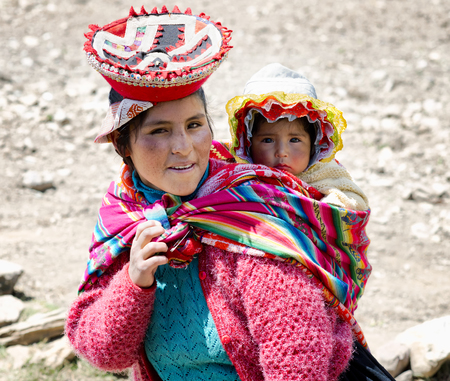 Close up of portrait of a smiling Quechua woman dressed in colourful traditional handmade outfit and carrying her baby in a sling. October 21, 2012 - Patachancha, Cuzco, Peru Editorial
