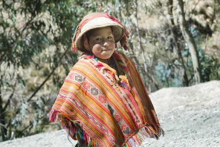 Smiling native peruvian boy wearing colorful handmade traditional poncho and a hat. October 21, 2012 - Patacancha, Cusco, Peru