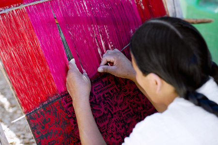 Inheemse Peruaanse vrouw weven ingewikkelde lama-wollen kleding met behulp van een traditionele handvlies