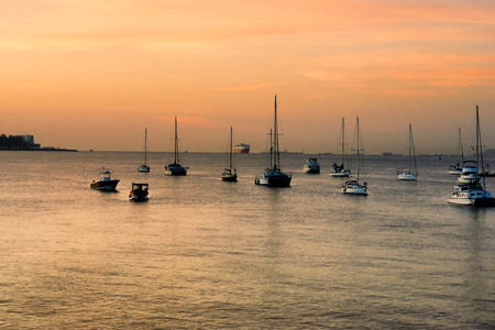 Sunrise over Panama Canal. Small boats moored and at far end ships waitng to go through the canal . Stock Photo