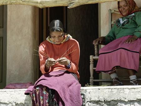 Smiling Tarahumara woman sitting outdoors and making pine-needle baskets. April 28, 2011 - Copper Canyon, Mexico Editorial