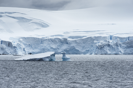 Low clouds over the snow capped mountains and chunks of ice floating at Admiralty Bay, King George Island, Antarctica Stock Photo