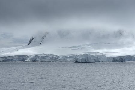 Sistema de nubes pesadas sobre la costa del puerto de Neko, bahía de Andvord, Península Antártica Foto de archivo