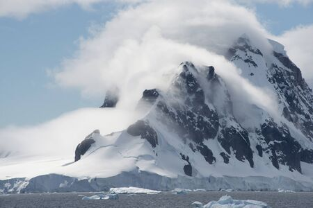 Antarctic Coastline With Snow Capped Mountains And Low Clouds 스톡 콘텐츠
