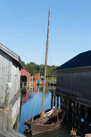 spar: Folk sailboat between boat houses