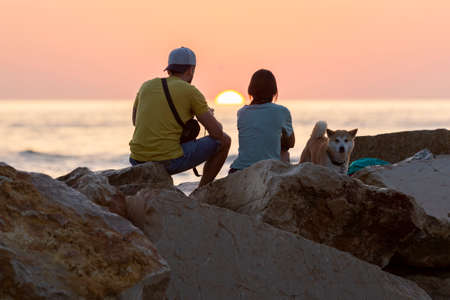 A young caucasian pretty couple and a dog sitting on the rocks during the sunrise