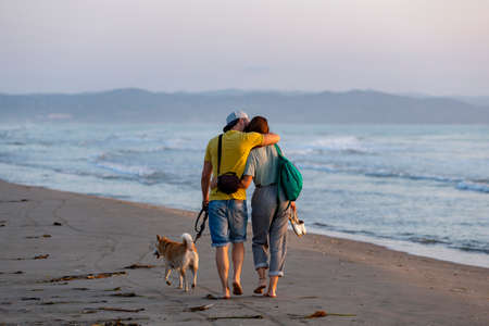 A young caucasian pretty couple and a dog walking and cuddling by the shore of the beach early in the morning
