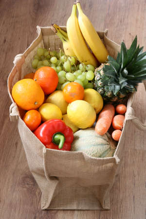 Assortment of various fruit and vegetable such as banana, pineapple, melon, orange, tomato and carrot in modern ecological bag.