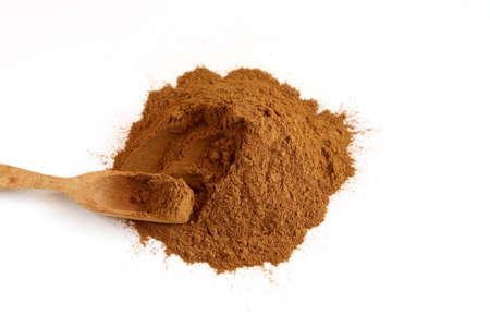cinnimon: Cinnamon powder on white background with woode spoon
