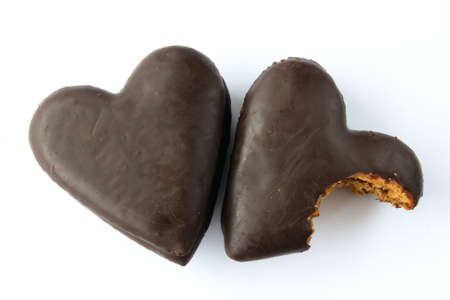 mordendo: Two gingerbread hearts covered with chocolate with jam filling, one partially bitten. Imagens