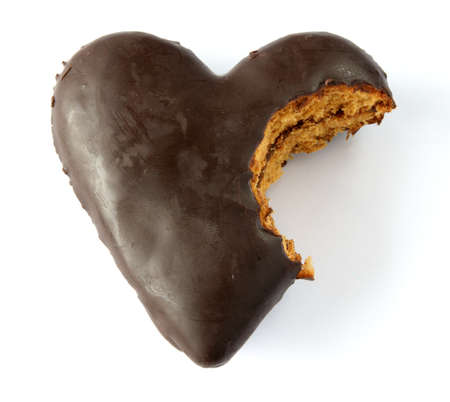 Single gingerbread heart covered with chocolate with jam filling, partially bitten.