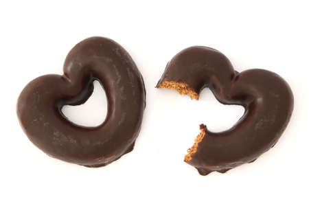 Two gingerbread hearts covered with chocolate, one partially bitten. photo