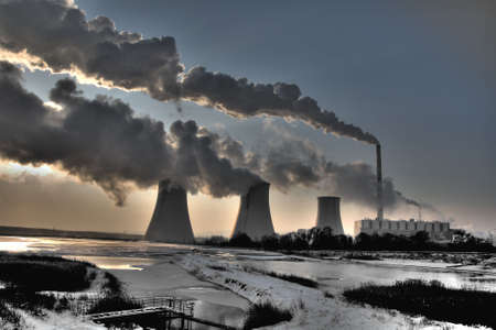 warming: Coal powerplant against sun with several chimneys and fumes Stock Photo