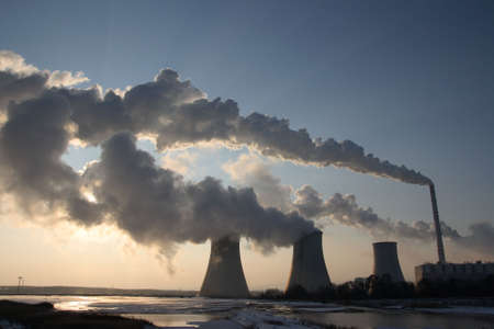 Coal powerplant view - against sun with several chimneys and huge fumes