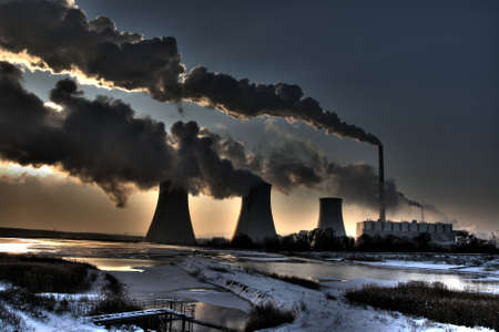 Coal powerplant - sun,  chimneys and fumes photo