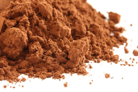 Dark cocoa powder scattered on white background - closeup view