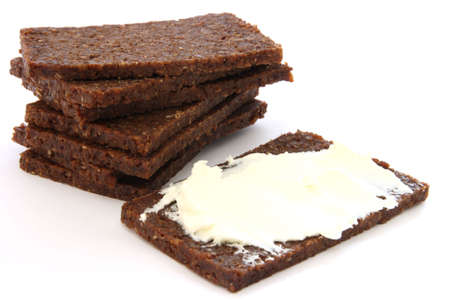Stack of black dark bread loafs called pumpernickel - specific german healthy whole corn read with fresh white cheese