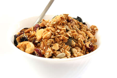 sesame: Baked muesli in white bowl with fruit and nuts on white background with a spoon