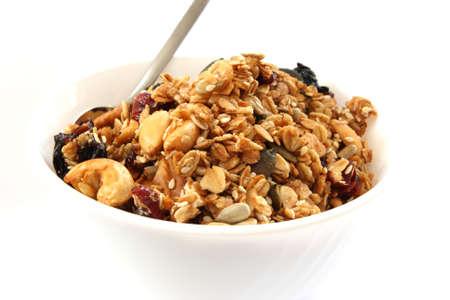 oatmeal: Muesli horneado en recipiente blanco con frutas y nueces sobre fondo blanco con una cuchara