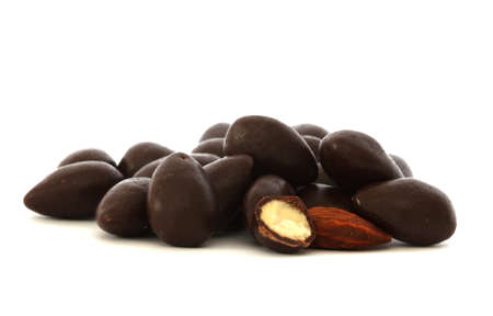 Almonds covered in dark chocolate - one cut in half and one naked (without chocolate) Stock Photo
