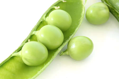 Fresh green pea in pod on white background - close up macro photo