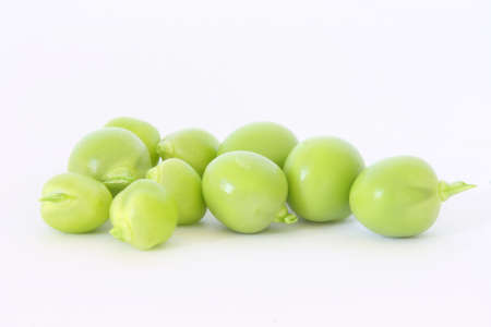 Fresh green peas scattered on white background - close up view