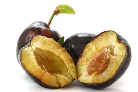 Three fresh plums on white background - one opened Stock Photo - 7718284