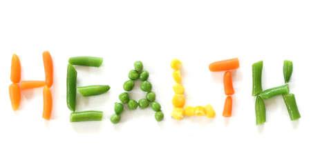 witaminy: Marchew, groch, kukurydza i zielona fasola stanowiących wyraz Health - Zamknij widok na białym tle w górę