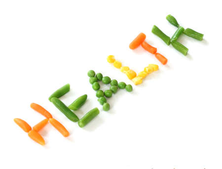 Carrot, pea, corn and green beans forming word health - close up view on white background photo