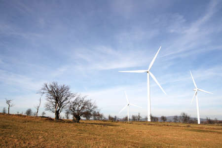 View of landscape with several windmills against blue sky generating power Stock Photo - 8582663