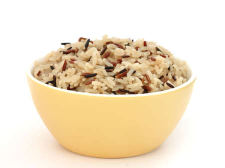 Close up view of cooked variety of rice sorts in yellow bowl - basmati and indian black Stock Photo