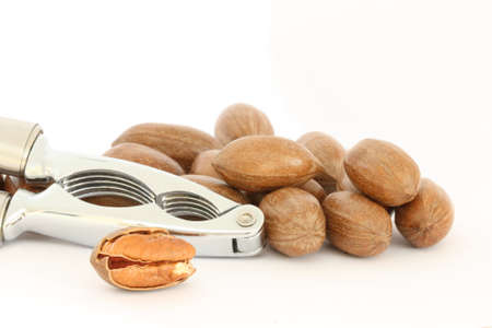 pekan: Detail view of pecan nuts and nut-cracker on white background