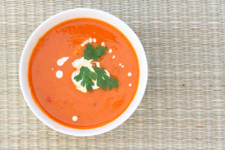 Top down view of red tomatoe soup in white bowl, sprinkled with cream