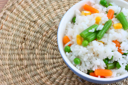 basmati: Close up view of cooked rice in bowl - with mixed of colorful vegetable on natural background Stock Photo