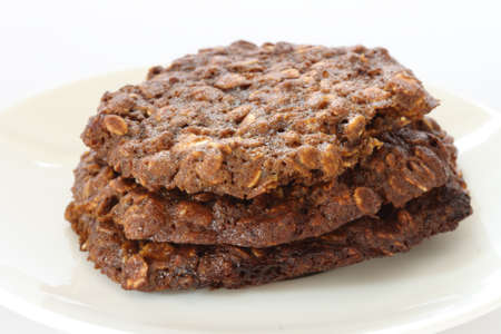 Stack of home made oatmeal cookies with molasses on white plate photo
