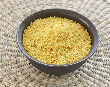 Close up view of couscous in brown bowl on natural wicker background