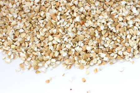 noone: Scattered view of dry raw pealed buckwheat on white background Stock Photo