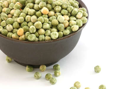 noone: Close up view of scattered dried green pea on white background and in bowl Stock Photo