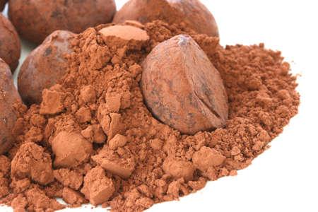 Шоколадный трюфель конфеты конфеты в какао-порошке кучу на белой тарелке и Backgroun