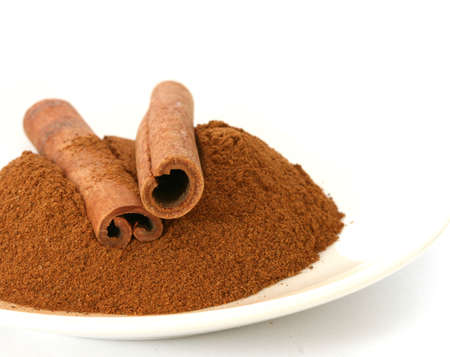 noone: Whole ground cinnamon and sticks on plate white background Stock Photo