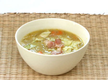 noone: Vegetable cabbage soup in white bowl with bacon pieces