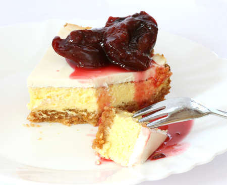 noone: Layered cheescake case on white plate and background with  cooked plums sauce Stock Photo