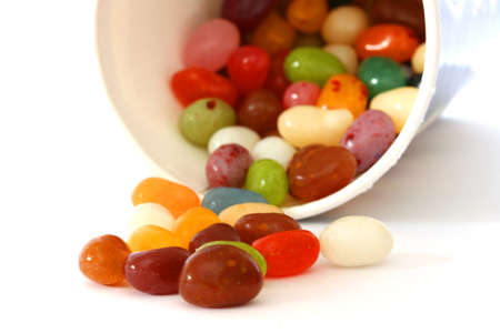 noone: Colourful candies in a pot and scattered on white background